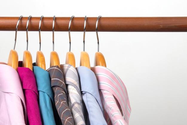 さまざまな女性のオフィスの古典的なシャツは、服を保管するためのハンガーに掛かっています