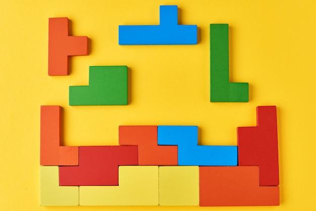 黄色の背景に異なる木製のブロック