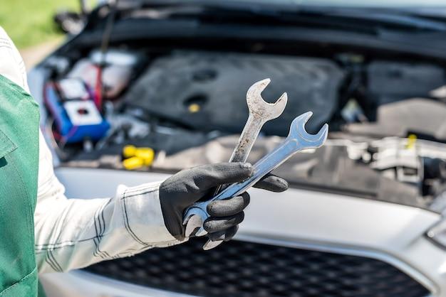 車のエンジンを手にしたさまざまなレンチとスパナ Premium写真