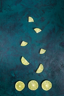 Differently cut lime slices laid out on emerald green background.