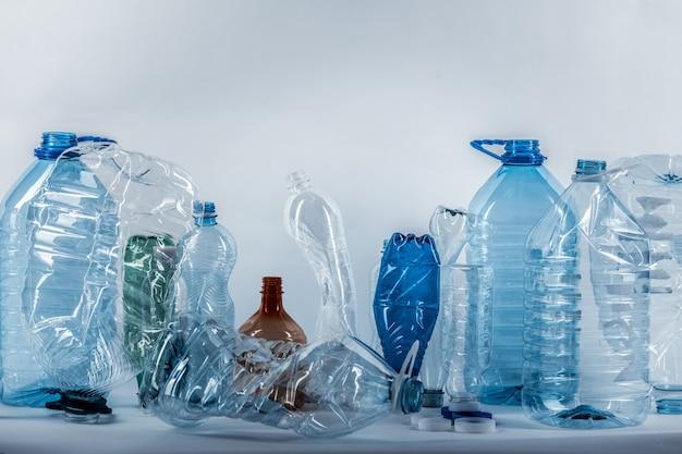 スタジオに配置されたさまざまなサイズのしわくちゃのプラスチック製の水筒