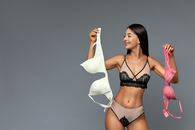 A difficult choice, a beautiful girl chooses a bra, holding bras of different colors in her hands. gray background, copy space, make difficult choices.