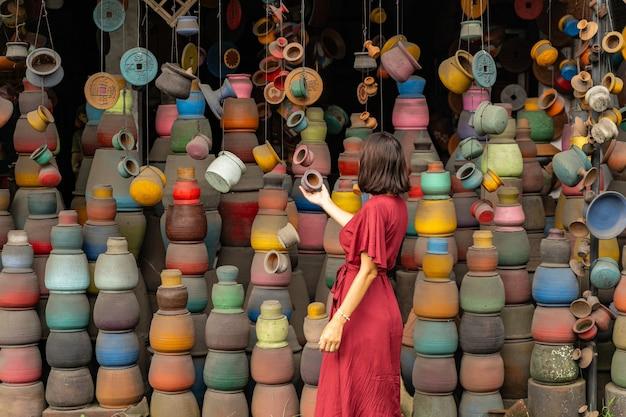 어려운 선택. 현지 시장을 걷는 동안 기념품 가게를 방문하는 기뻐하는 젊은 여성