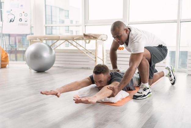 어려운 운동. 좋은 유쾌한 남자가 바닥에 누워 어려운 신체 운동을하고 있습니다.