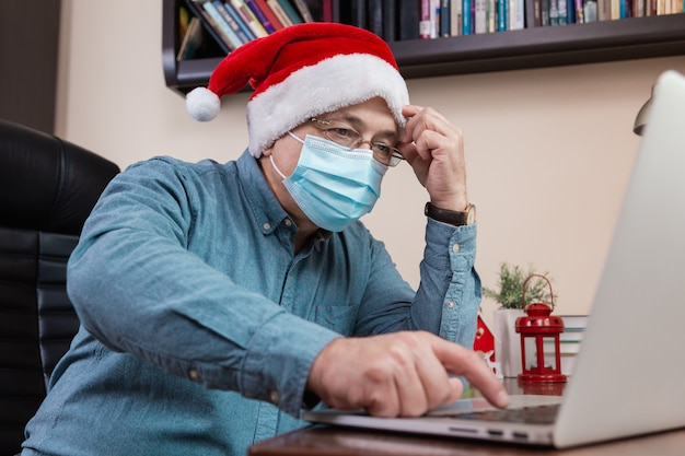Difficult senior man in santa claus hat talks using laptop for video call friends and childrens. the room is festively decorated. christmas during coronavirus.