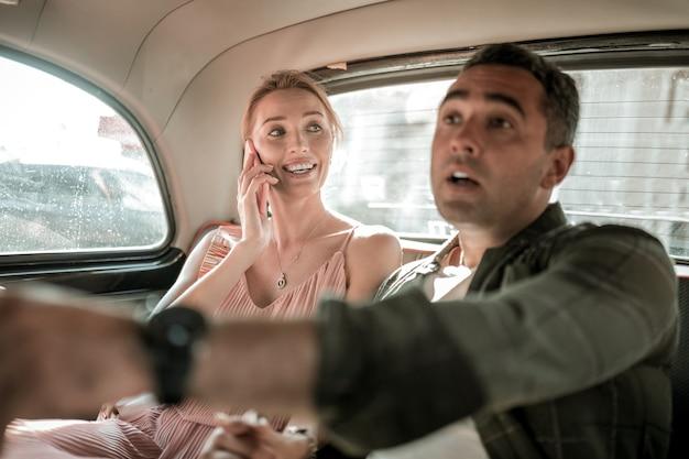 어려운 방법입니다. 걱정스러운 남자는 아내와 함께 차 뒷좌석에 앉아 운전사에게 길을 가리킬 곳을 설명하고 있습니다.