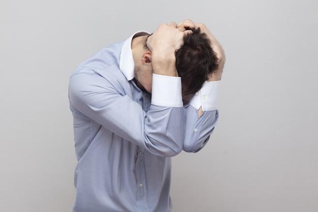 어려움, 실패 또는 실수. 서 있고 그의 머리를 잡고 고전적인 밝은 파란색 셔츠에 잘생긴 강모 사업가의 초상화. 실내 스튜디오 촬영, 회색 배경 copyspace에 격리.