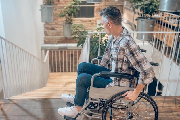 어려움. 휠체어에 격자 무늬 셔츠와 청바지를 입은 젊은 성인 남성이 실내 계단을 내려다보고 있습니다.