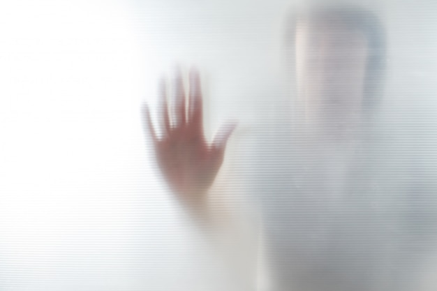 Diffused silhouette of female hands, view with shadow through plastic