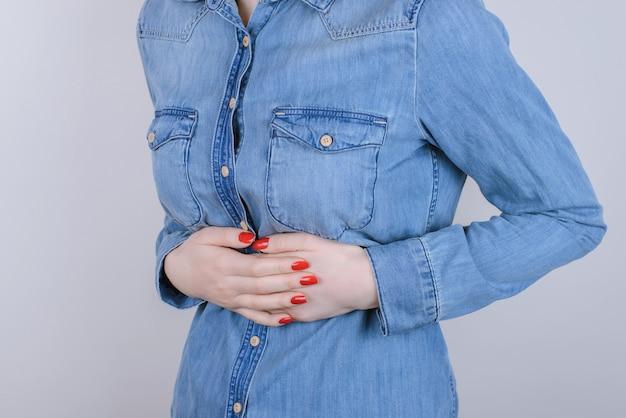 消化不良消化不良人人のコンセプト。灰色の背景に分離された腹痛に苦しんでいる悲しい不幸なストレスのうつ病の女性のトリミングされたクローズアップ写真
