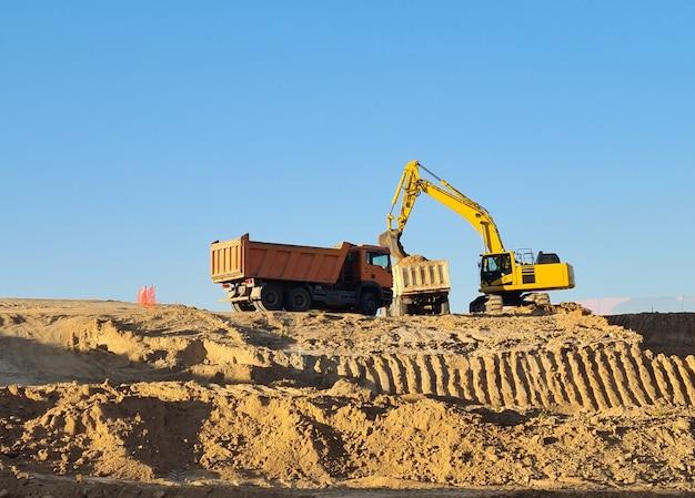 晴れた日に建設現場で2台のトラックを操作する掘削機。マドリードのバルデベバスで働く掘削機。