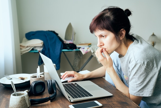 デジタル中毒、パニックの女性はインターネットでコロナウイルスに関する記事を読みます。
