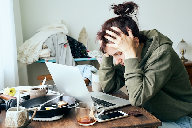 Digital addiction, woman in panic and stress, abandoned household chores,