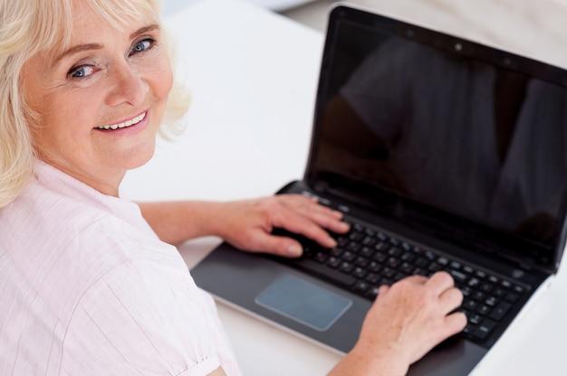 디지털 시대 선배. 카메라를 보고 노트북 작업을 하는 동안 웃고 있는 쾌활한 시니어 여성의 상위 뷰