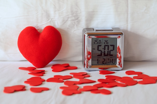 Digital alarm clock and heart shape on white bed sheet against the pillow, sleep well concept