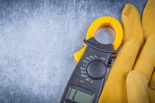 金属の背景にデジタル電流計保護手袋