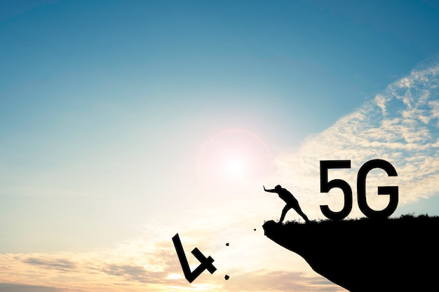 デジタルとテクノロジーの変革の概念。男は4gを5gテクノロジーに変えるために崖から4番を押します。