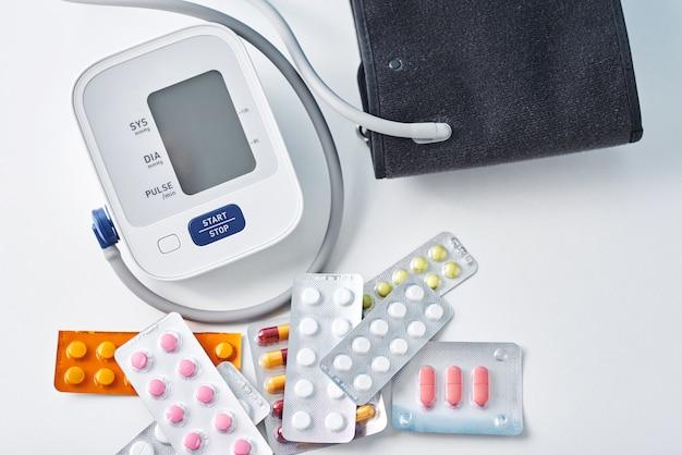 デジタル血圧モニターと白いテーブルの上の医療薬。ヘルスケアおよび医学の概念