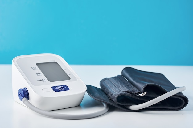 Digital blood pressure monitor on blue background