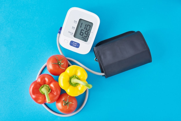Digital blood pressure monitor and fresh vegetables on blue background. healthcare concept