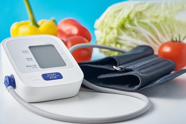 Digital blood pressure monitor and fresh vegetables on table against blue background. healthcare concept