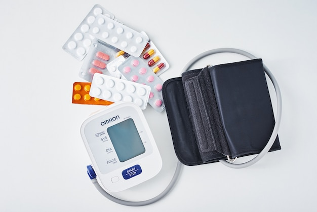 Digital blood pressure monitor and medical pills on white table. healthcare and medicine concept