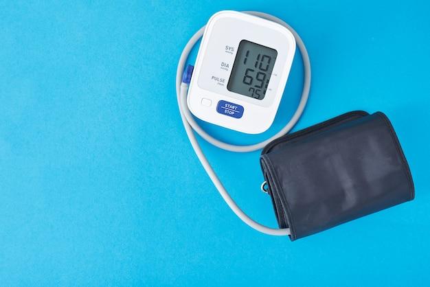 青色の背景は、クローズアップのデジタル血圧モニター。ヘルスケアと医療のコンセプト