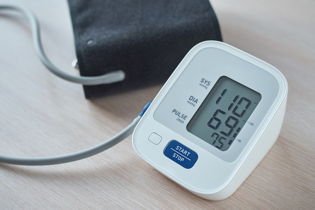 Digital blood pressure monitor on table, closeup. helathcare and medical concept