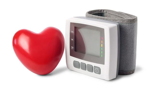 Digital blood pressure monitor (tonometer) and red heart near, isolated on white background.