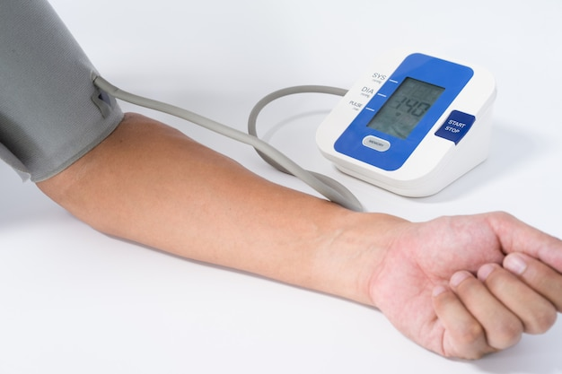 Digital blood pressure monitor with the arm of a man on white