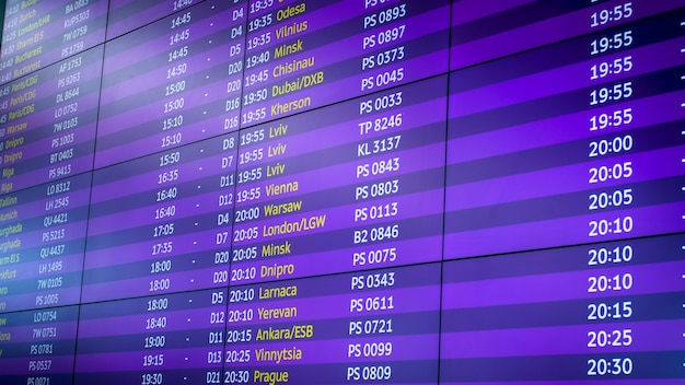 Digital board with schedule of airplane flights in airport.