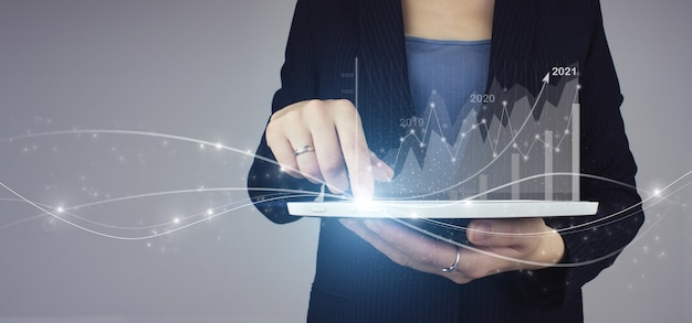 Digital business and stock market. white tablet in businesswoman hand with digital hologram financial charts showing growing revenue in 2021 on grey. successful international financial investment.