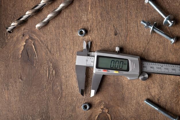 ハードウェアが付いている木のテーブルの上のデジタルノギス