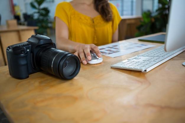 Цифровая камера за столом и за работой графического дизайнера