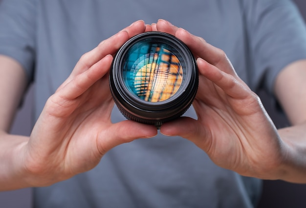 Digital camera lens with beautiful studio softbox reflecting in hands of female photographer.
