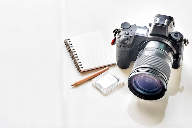 Digital camera and notebook on white table with copy space.