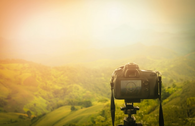 Digital camera professional / camera on tripod with view of mountain nature on background - take photos shooting nature