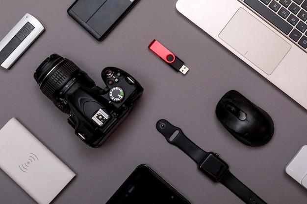 Цифровая камера, usb с внешним жестким диском или аккумулятором и оборудование профессионального фотографа на серой бумаге