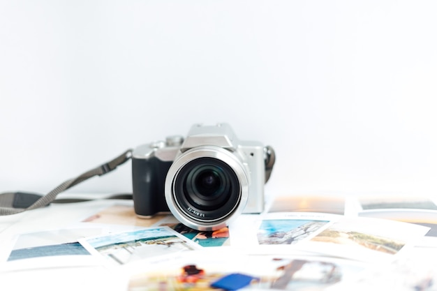 Digital camera on white background and photos scattered on the study table.