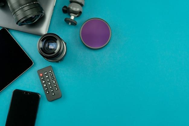青い紙の背景にプロの写真家のレンズと機器を備えたデジタルカメラ