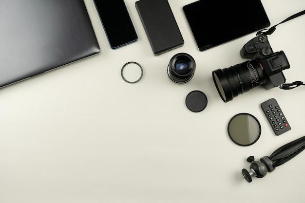 白い背景の上のプロの写真家のレンズと機器を備えたデジタルカメラ