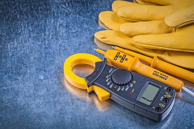 引っかき傷のある金属の背景の電気の概念のデジタルクランプメーター電気テスター保護手袋。