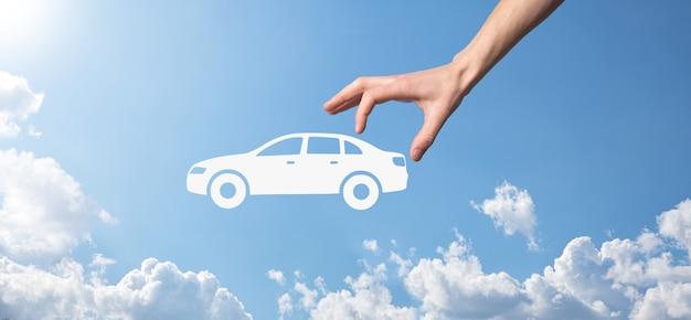 Цифровая композиция человека, держащего автомобиль значок. автомобильное страхование и концепция автосервисов. бизнесмен с жестом предложения и значком автомобиля