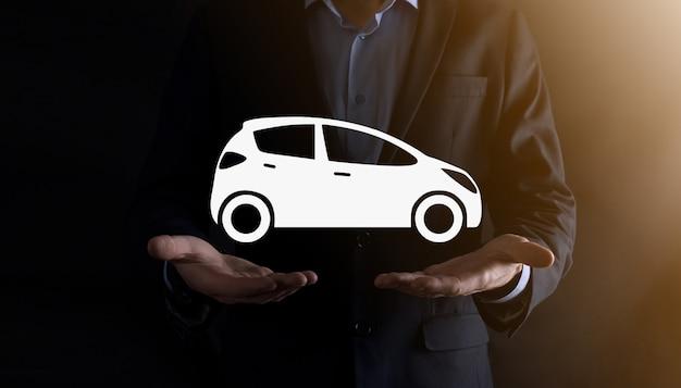 車のアイコンを保持している人のデジタル合成。自動車保険と自動車サービスの概念。車のジェスチャーとアイコンを提供するビジネスマン