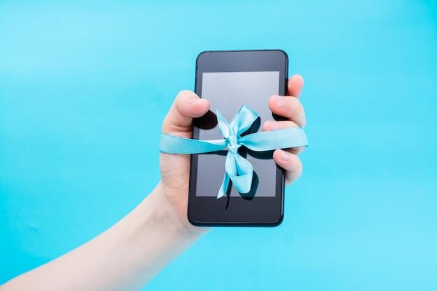 デジタルデトックスコンセプト。青いリボンで結ばれたスマートフォンを持つ子供の手。ガジェット中毒