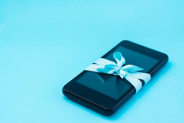 Концепция цифрового детоксикации. смартфон перевязан голубой лентой с бантом на синем фоне. зависимость от гаджетов