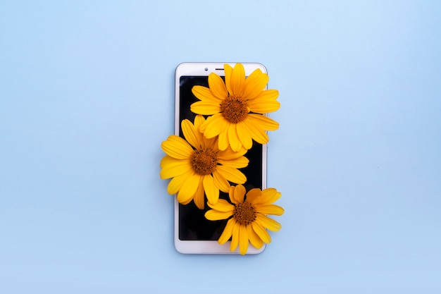 Digital detox concept. yellow flowers on a smartphone with copy space.