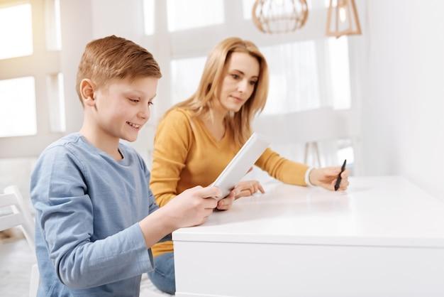 Цифровое устройство. радостный счастливый позитивный мальчик сидит за столом и улыбается во время использования планшета