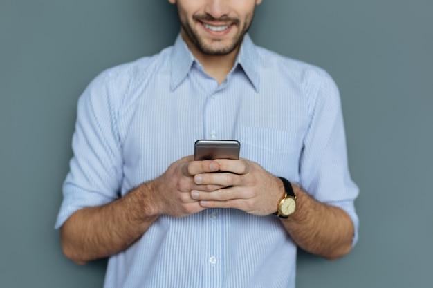 デジタルデバイス。素敵な楽しい若い男の手にある革新的なスマートフォンの選択的な焦点