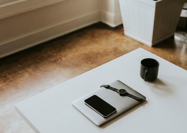 책상 위의 커피잔 옆에 있는 디지털 기기